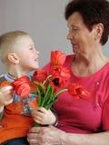 De huidige bloemen van de kleinzoon aan grootmoeder stock afbeeldingen