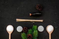 De huidzorg en ontspant Schoonheidsmiddelen en aromatherapy concept Pine spa zout, olie, nette tak en pinecones op zwarte royalty-vrije stock foto