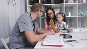 De huisarts schrijft de benoeming van een klein meisje voor Moeder en dochter bij een ontvangst bij de huisarts stock footage