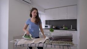De huishoudenplichten, blij huishoudstermeisje met ijzer maakt verse handdoeken op strijkplank glad en de pret zingt en danst stock footage