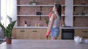 De huishoudenplichten, grappig huishoudstermeisje die pret hebben en zingt in bezem zoals microfoon tijdens het algemene schoonma stock footage