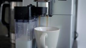De huiskoffie die machine maken produceert cappuccino in keuken die in ochtend, hete drank in een kop gieten stock videobeelden