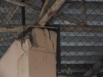 De huispijlers die het gewicht van de grote dakstructuur dragen zijn gebroken stock afbeelding