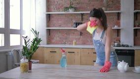 De huisroutines, glimlachend huisvrouwenmeisje in rubberhandschoenen voor het schoonmaken wrijft vuil meubilair met chemie stock video
