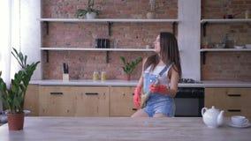 De huisroutines, het blije huishoudstervrouw dansen en zingt in bezem zoals microfoon tijdens huishoudenplichten stock videobeelden