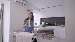 De huisroutines, vrolijk huisvrouwenmeisje strijkt verse handdoeken en het hebben van pret en het zingen stock footage