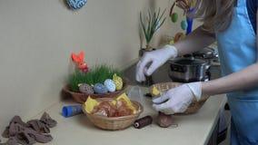 De huisvrouw bereidt paaseiverf met rijstkunst in voor keuken 4K stock videobeelden