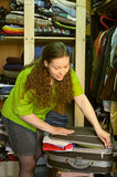 De huisvrouw in de garderobe pakt een koffer in Royalty-vrije Stock Afbeelding