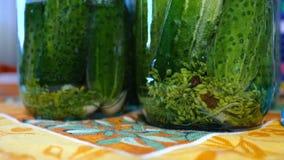 De huisvrouw giet hete marinade in een glaskruik met komkommers stock video
