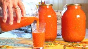 De huisvrouw giet vers gebrouwen tomatesap in een glaskop stock footage