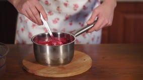 De huisvrouw kookt zoete saus van rode kersen in een kom, zich mengt door lepel stock video