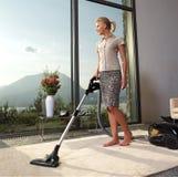 De huisvrouw maakt thuis huishoudelijk werk Stock Fotografie