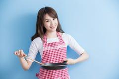 De huisvrouw neemt wok en lepel Stock Foto