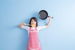 De huisvrouw neemt wok en lepel Stock Afbeelding