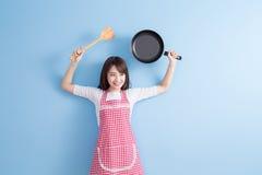 De huisvrouw neemt wok en lepel Stock Fotografie