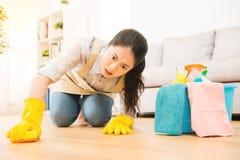 De huisvrouw schrobt nauwelijks schoonmakende vloer Stock Foto's