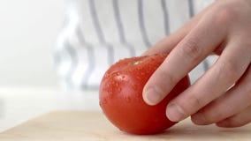 De huisvrouw snijdt een tomaat in stukken op een houten raad in langzame motie stock footage