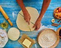 De huisvrouw snijdt het deeg in stukken driehoekige vorm Stock Afbeelding