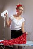 De huisvrouw strijkt de blouse Stock Afbeelding
