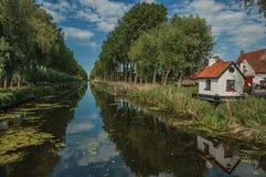 De huizen, de struiken en het bosje langs kanaal met hemel overdachten water, in de recente middag lichte en blauwe hemel, dichtb royalty-vrije stock fotografie