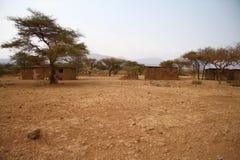 De huizen van Afrika in droog land Stock Fotografie