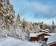 De huizen van het logboek in sneeuw de winterlandschap Stock Fotografie