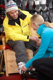 De Hulp Helpende Mens van de verkoop om op de Laarzen van de Ski te proberen Royalty-vrije Stock Foto's
