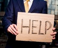 De Hulp van het de holdingsteken van de zakenman in openlucht Stock Foto