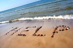 De HULP van Word op strandzand stock foto