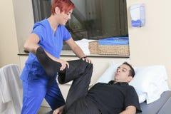 De hulpcliënt van de fysiotherapeutvrouw bij baan Stock Fotografie