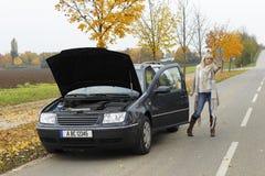 De hulpeloze vrouw probeert om een auto op de straat tegen te houden Stock Foto