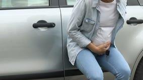 De hulpeloze zwangere vrouw heeft mislukking, eenzame dichtbijgelegen auto, voorbarige geboorte stock footage