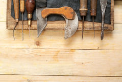 De hulpmiddelen van de leerambacht op houten achtergrond Het bureau van het Craftmanswerk Stuk huid en met de hand gemaakte hulpm Stock Foto