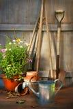 De hulpmiddelen van de tuin en een pot van de zomerbloemen in loods Stock Foto