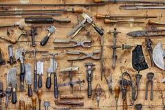 De hulpmiddelen van een looier op de muur in een looierij Stock Afbeelding
