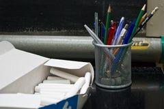 De hulpmiddelen van het klaslokaal: krijt en potloden Stock Afbeelding