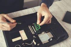 De hulpmiddelen van de mensenhand met gebroken notitieboekje stock afbeelding