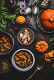 De de hutspotschotel van de veganistpompoen met spinazie diende in kom met lepel op de donkere achtergrond van de keukenlijst met Stock Foto's