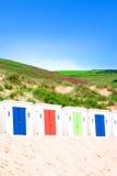 De hutten van de zon langs zandig strand stock foto's