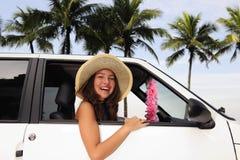 De huur van de auto: gelukkige vrouw in haar auto dichtbij het strand royalty-vrije stock foto