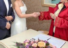 De huwelijksarchivaris wenst nieuw paar geluk en geeft de familieregistratie aan de bruid royalty-vrije stock afbeeldingen