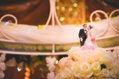 De huwelijkscake, beeldjes van de bruid en de bruidegom op een huwelijk koekt Stock Fotografie