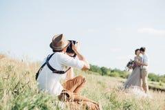 De huwelijksfotograaf neemt beelden van bruid en bruidegom in aard, fijne kunstfoto