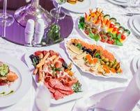De huwelijkslijst diende met smakelijke maaltijd, het koude vlees van de antipastoschotel, vissenschotel, kaasschotel Het menu va royalty-vrije stock fotografie