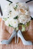 de huwelijksschoenen en het boeket van witte Tuin namen pioen toe Stock Fotografie
