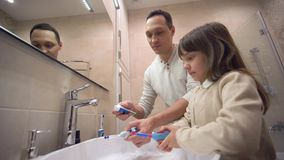 De hygiëne van de kinderenochtend, jonge vader onderwijst dochter om tanden te borstelen en mondelinge gezondheid voor spiegel hi stock footage