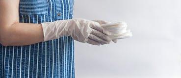De hygi?neproducten van het wijfje Vrouw die in medische handschoenen een stapel maandverbanden houden tegen witte achtergrond Pe stock fotografie