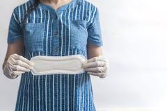De hygi?neproducten van het wijfje Vrouw die in medische handschoenen sanitaire stootkussens houden tegen witte achtergrond Het c royalty-vrije stock afbeeldingen