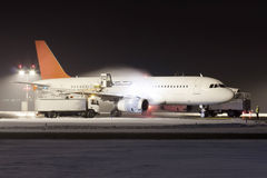 De-icing. White plane with red tail during de-icing in winter Royalty Free Stock Photography