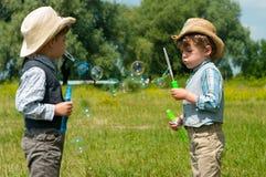 De identieke tweeling blaast zeepbels Stock Fotografie